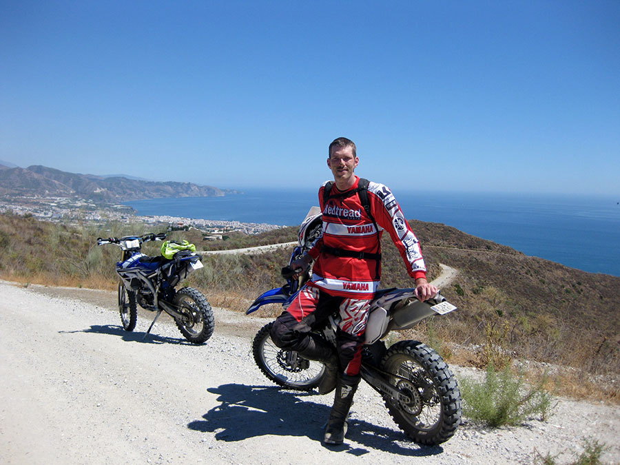 a Readtread rider stopping for a photograph in andalucia during an off road motorcycle tour. Sea and coastline featured in the background as they are high on the dirt trail..