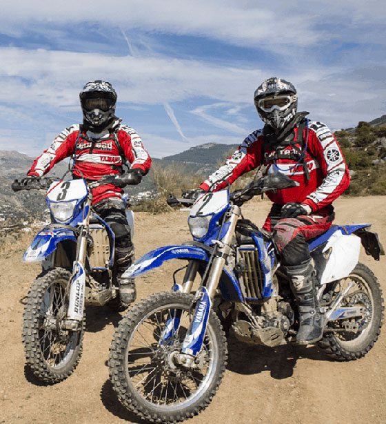 Two people on a Yamaha motorbikes during a break for a photo during an off road trail riding tour in Spain organised by Readtread