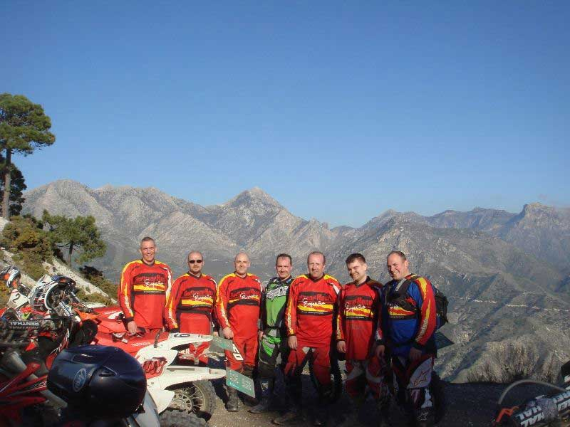 A team of guys posing with dirt bikes during an off road motorcycle tour in Spain organised by Redtread.
