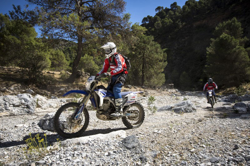Bikers making it uphill on a trail, off road motorcycle tours in Spain organised by Redtread.